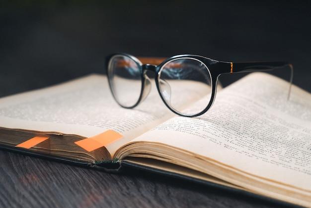 Na mesa de madeira está um livro aberto