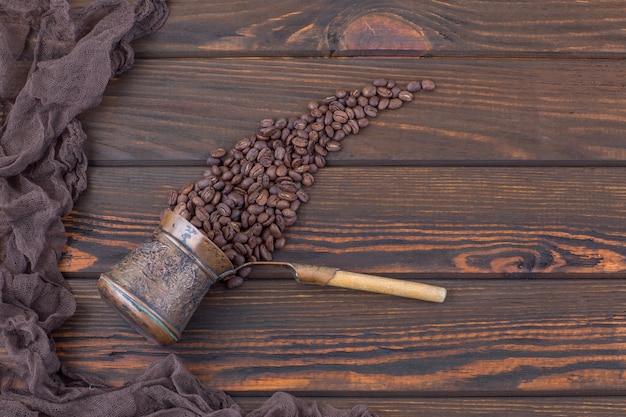 Na mesa de madeira há uma cafeteira velha, grãos de café derramam dela