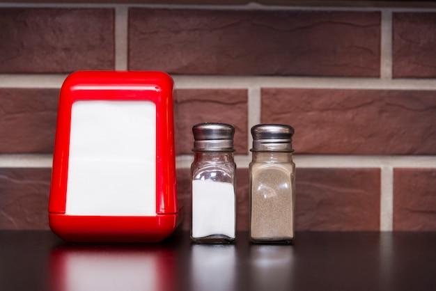 Na mesa do café, há um porta-guardanapos vermelho, uma salina e uma caixa de pimenta.