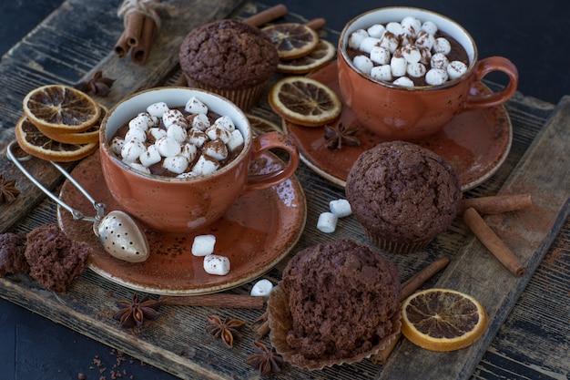 Na mesa, duas xícaras de chocolate quente e marshmallows, muffins de chocolate e decoração