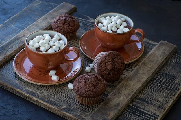 Na mesa, duas xícaras de chocolate quente e marshmallows, muffins de chocolate