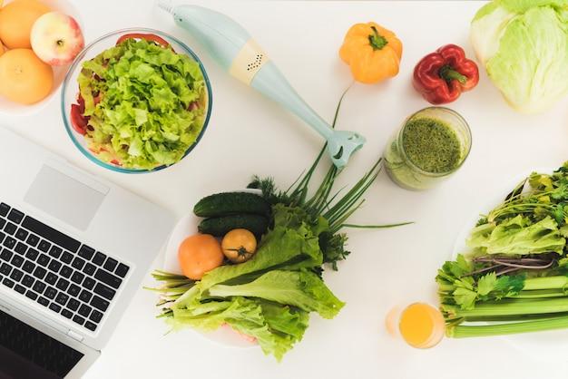 Na mesa é um laptop, ao lado do qual se encontra uma variedade de frutas