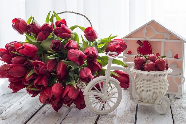 Na mesa em uma cesta há muitas tulipas vermelhas e uma cesta com morangos