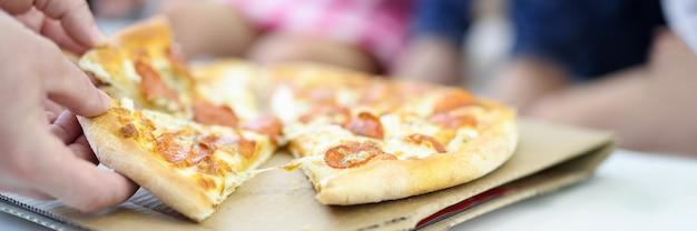 Na mesa está a pizza, cortada em pedaços, a mão do homem segura duas pilhas