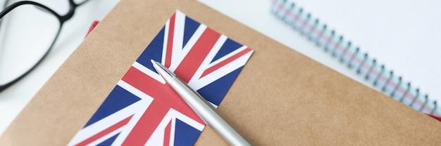 Na mesa está o diário com a bandeira britânica e a caneta, aprendendo línguas estrangeiras a partir do conceito do zero