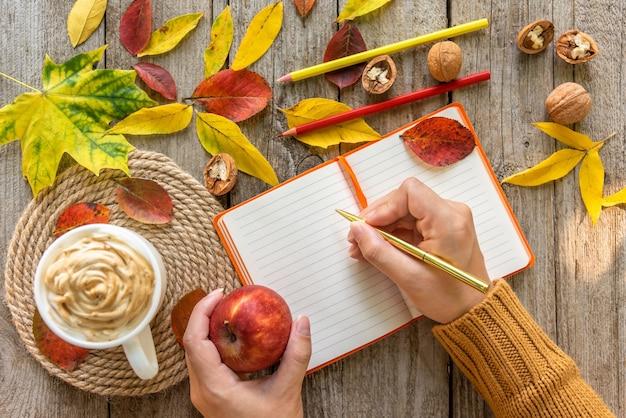 Na mesa está um caderno em uma manhã de outono com uma xícara de café