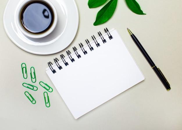 Na mesa está uma xícara branca com café, uma planta verde e clipes de papel, uma caneta e um caderno em branco com local para inserir texto