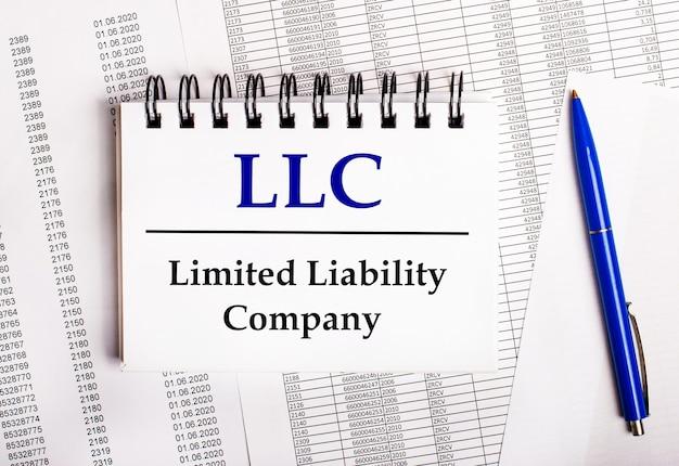 Na mesa estão gráficos e relatórios, nos quais estão uma caneta azul e um bloco de notas com a palavra llc limited liability company