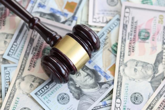 Na mesa estão notas americanas com o martelo de madeira de um juiz. conceito de dívida de oficiais de justiça
