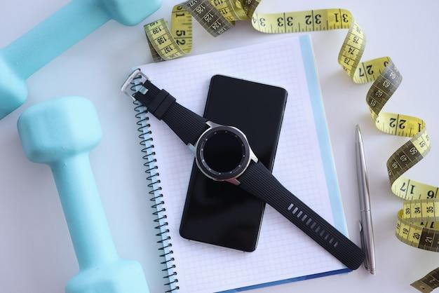 Na mesa estão o planejador diário, smartphone, relógio inteligente, halteres e centímetros