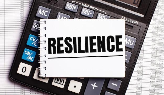 Na mesa estão os relatórios, uma calculadora e um cartão com a palavra resiliência. conceito de negócios