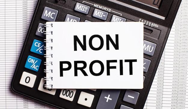 Na mesa estão os relatórios, uma calculadora e um cartão com as palavras non profit. conceito de negócios