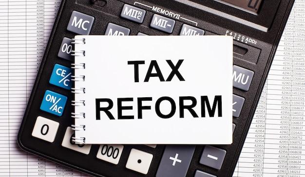 Na mesa estão os relatórios, uma calculadora e um cartão com as palavras reforma tributária. conceito de negócios
