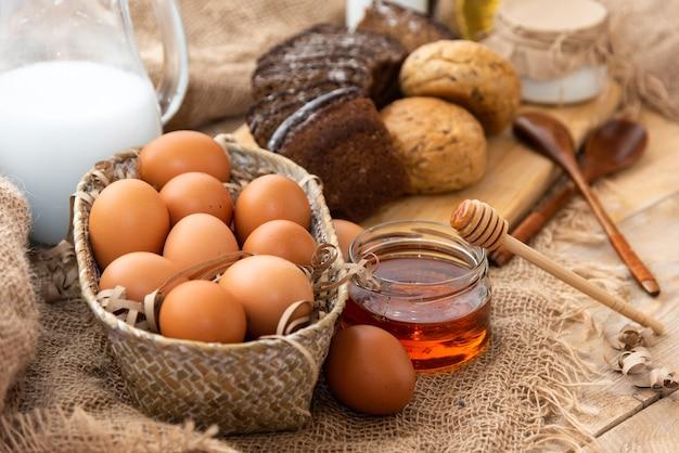 Na mesa estão produtos naturais caseiros. leite, ovos de galinha, mel e creme de leite.