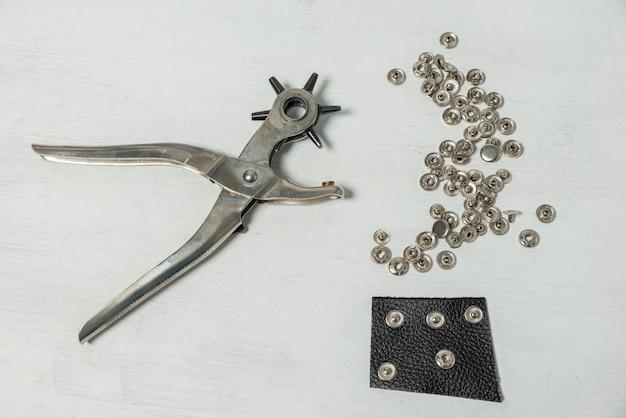 Na mesa, há um furador para instalar botões e outros pequenos detalhes