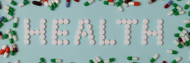 Na mesa há uma inscrição saúde em torno de comprimidos.