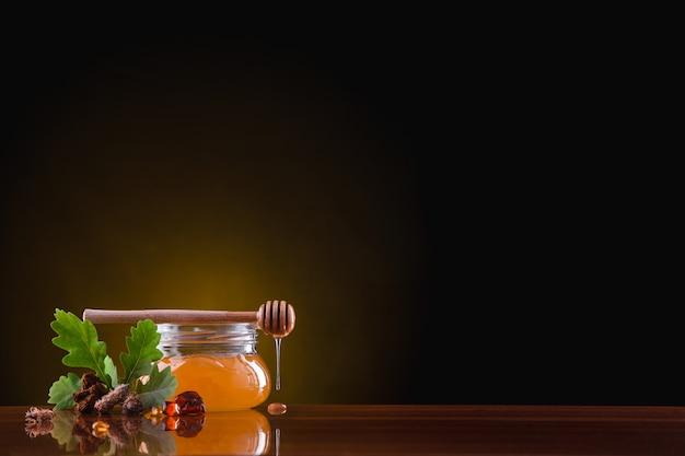 Na mesa há uma jarra de vidro com mel no escuro