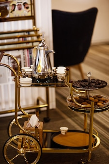Na mesa móvel, tâmaras frescas, chá e doces orientais
