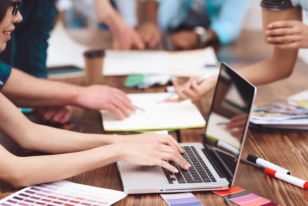 Na mesa na frente de um grupo de jovens é um laptop