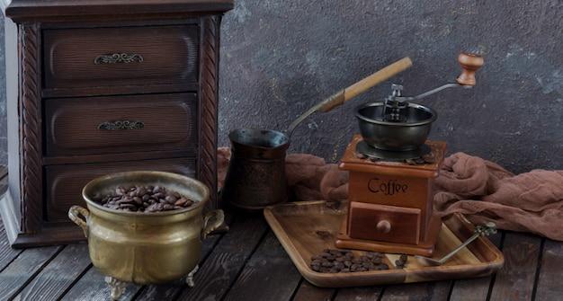 Na mesa um moedor de café, um armário, um turco, café e grãos de café