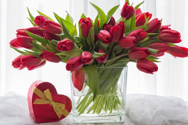 Na mesa um vaso com tulipas vermelhas e uma caixa vermelha com um presente em forma de um coração