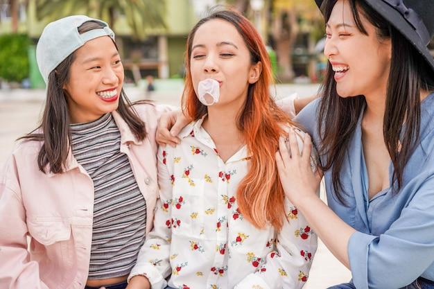 Na moda asiáticas meninas se divertindo juntos ao ar livre