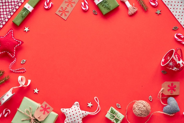 Na moda eco friendly zero resíduos decorações de ano novo de natal e presentes embalados. plano geométrico leigos, vista superior em papel vermelho com estrelas de têxteis, caixas de presente e bastões de doces. moldura com cópia-espaço.
