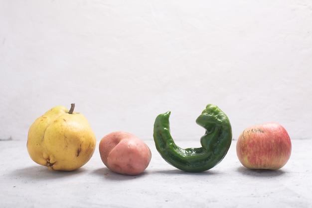 Na moda feias frutas e legumes orgânicos em cima da mesa