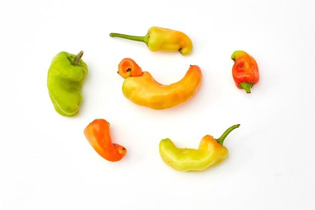 Na moda feias frutas e legumes orgânicos. pimentas em branco. produtos deformados, frutas e vegetais deformados, desperdício de alimentos. vista superior, flatlay.