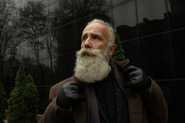 Na moda homem sênior com cabelos grisalhos e barba é ao ar livre na rua.