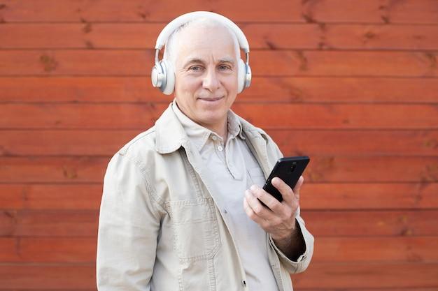 Na moda homem sênior usando smartphone app com fundo vermelho. macho maduro moda se divertindo com as novas tendências da tecnologia. tecnologia e alegre estilo de vida idoso conceito