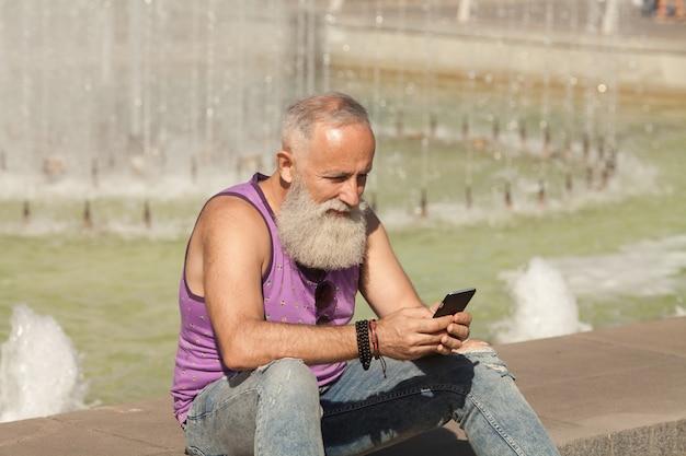 Na moda homem sênior usando smartphone no centro da cidade ao ar livre - moda masculina madura se divertindo com as novas tendências da tecnologia - tecnologia e alegre conceito de estilo de vida idoso