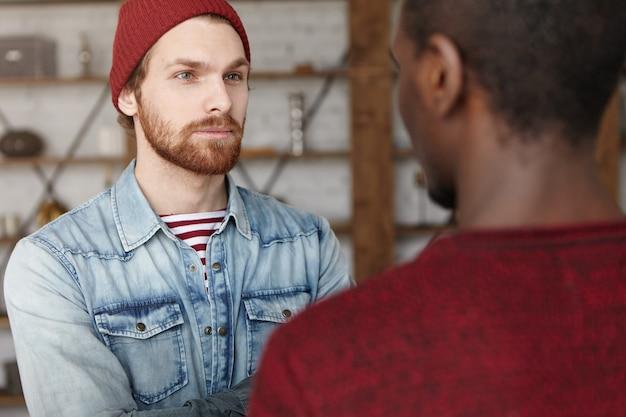 Na moda jovem barbudo homem caucasiano vestindo moda chapéu e camisa jeans, sorrindo enquanto tendo uma boa conversa com o homem de pele escura irreconhecível durante reunião no interior do restaurante moderno