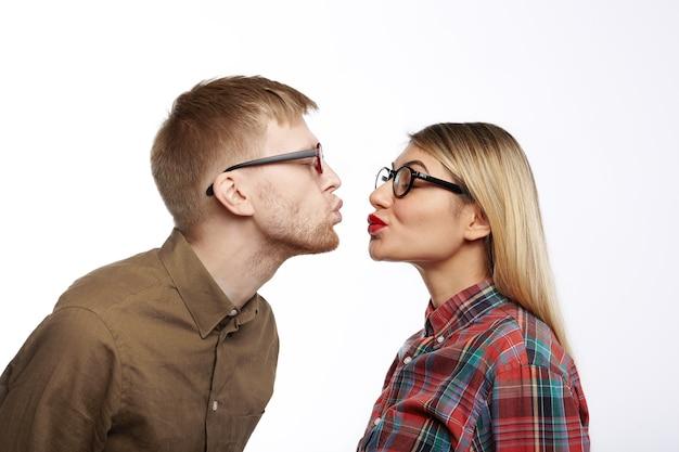 Na moda jovem macho com barba por fazer e linda fêmea elegante fazendo beicinho seus lábios e fechando os olhos, prestes a beijar. retrato de lado de casal fofo e doce hippie apaixonado se preparando para se beijar