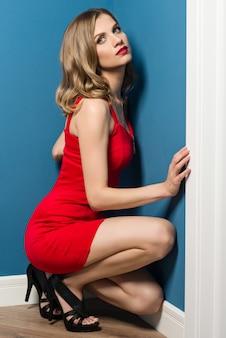 Na moda jovem menina loira de vestido vermelho