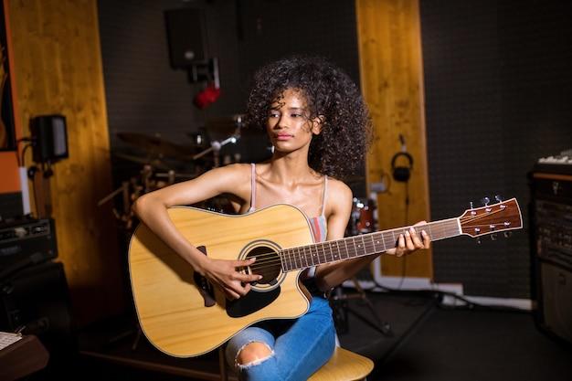 Na moda jovem negra em jeans designer modernos, sentado tocando violão em um estúdio de gravação