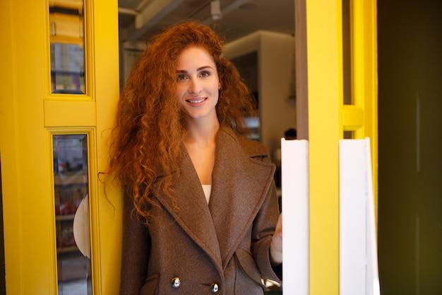 Na moda jovem saindo de uma cafeteria