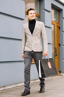 Na moda jovem segurando o saco de compras com etiqueta de venda