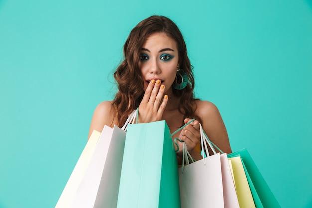 Na moda jovem vestindo moda estilo segurando sacolas de papel colorido com compras