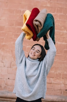 Na moda jovem, vestindo um suéter cinza de malha está sorrindo e se divertindo enquanto segura blusas coloridas