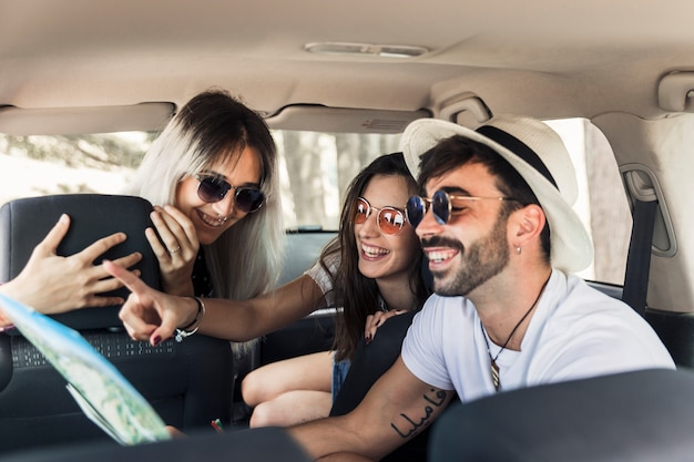 Na moda jovens amigos sentado dentro do carro moderno, olhando para o mapa