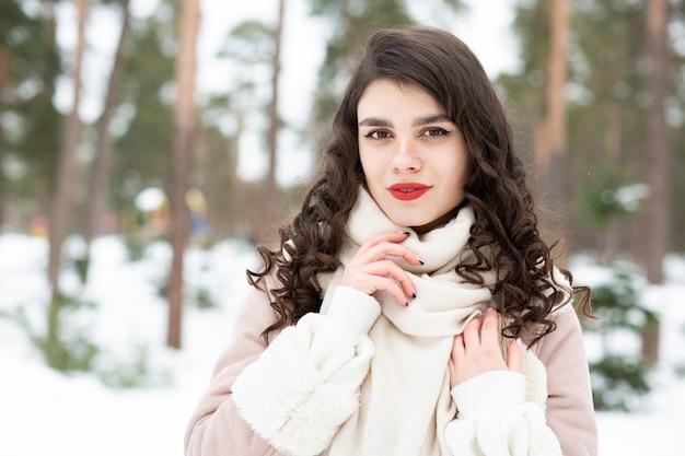 Na moda mulher morena com cabelo comprido usa casaco no inverno. espaço para texto