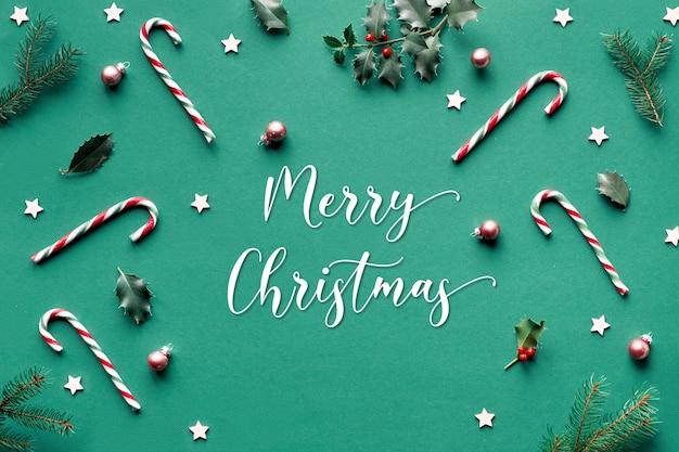Na moda natal plana geométrica leigos na superfície de papel verde com bastões de doces, galhos de azevinho e abeto, estrelas de madeira e bugigangas de vidro, texto