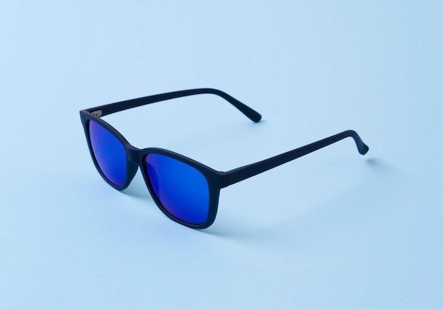 Na moda óculos de sol modernos na mesa azul.