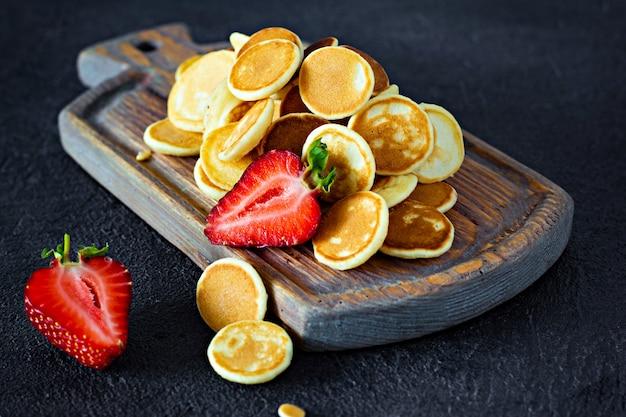 Na moda pequeno-almoço em casa com pequenas panquecas (mini panquecas) com morangos e hortelã em uma placa de madeira sobre um fundo escuro.