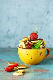 Na moda pequeno-almoço em casa com pequenas panquecas (mini panquecas) com morangos e hortelã em uma tigela (xícara) sobre um fundo azul.