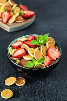 Na moda pequeno-almoço em casa com pequenas panquecas (mini panquecas) com morangos e hortelã em uma tigela (xícara) sobre um fundo escuro.