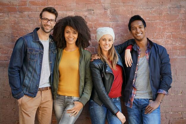 Na moda pessoas em frente a parede de tijolos