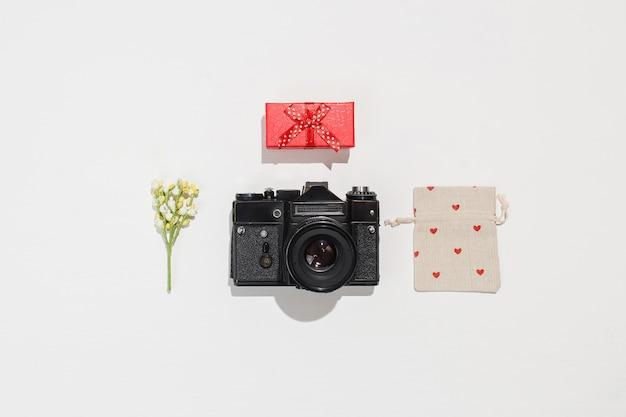 Na moda plana leiga composição com câmera retro, caixa de presente vermelha, saco de lona de presente com formas de coração vermelho e flor de campo de primavera no fundo branco