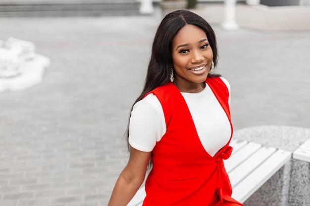 Na moda positiva jovem africana com um sorriso incrível em um elegante terno vermelho sentado e sorrindo no banco de madeira vintage na cidade na primavera. modelo atraente linda garota negra feliz ao ar livre.